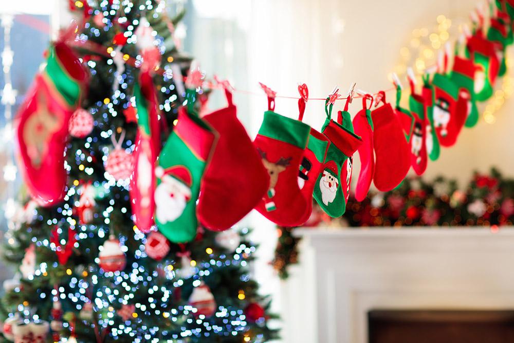 ghirlanda-calze-natalizie-ingrosso-con-albero-natale-sfondo