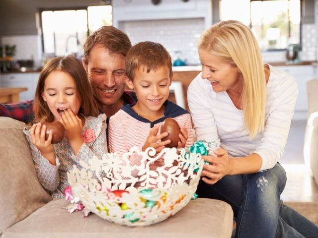 famiglia-mangia-uova-e-ovetti-di-cioccolato-nel-salotto-di-casa-a-pasqua
